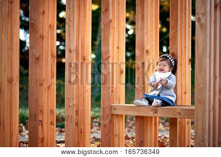 Baby girl sitting on the wood bench