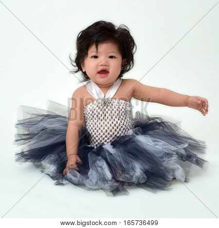 Cute Asian baby girl in flare dress sitting up.