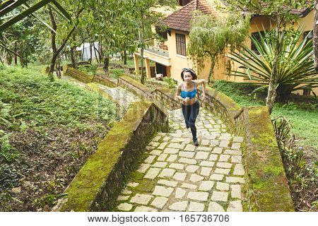 Young Vietnamese woman jogging along the steps in the morning