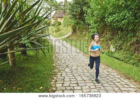 Pretty young Vietnamese woman jogging in park