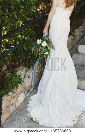 Bride in a beautiful long white wedding dress holding a bouquet of flowers