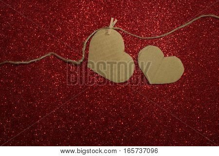 Two carton heart attached to the rope on red shining background