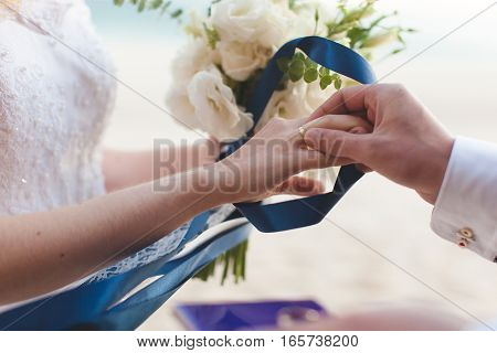 The groom wears a wedding ring on the finger of the bride close-up