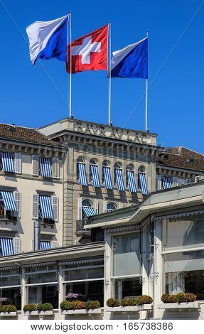 Zurich, Switzerland - 20 April, 2016: upper part of the Baur au Lac Hotel building decorated with flags of Zurich and Switzerland. The Baur au Lac Hotel is a luxury hotel in Zurich, founded in 1844 by Johannes Baur.