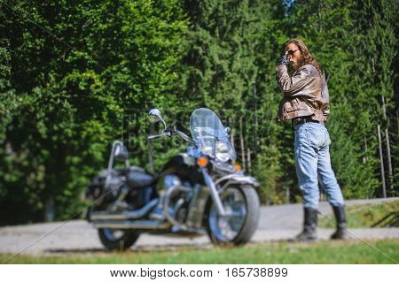 Biker Standing By His Custom Made Cruiser Motorcycle