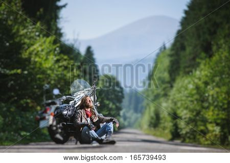 Male Biker Sitting On Road Near Motorcycle