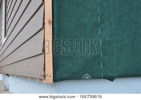 Close up on corner thermal insulation of a house wall on a building site. Construction or repair of the rural houseplastic siding fixing facade membrane insulation house wall.