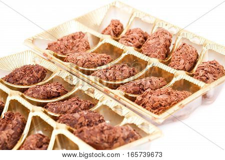 Truffle chocolate in plastic box on white background.