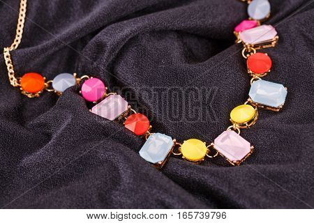 Stylish necklace with colorful stones on black fabric background.