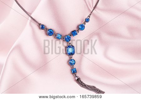 Stylish necklace on the pink fabric background.