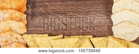 Frame of crunchy cookies and potato crisps on rustic board concept of restriction eating unhealthy and salted food copy space for text or inscription