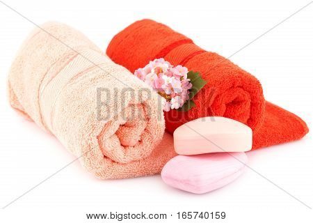 Colorful rolled towels with flowers and soaps isolated on white background.