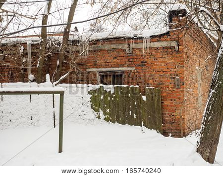 The old brick building behind a wooden fence in winter.