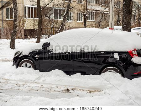 Black car strewn with snow after a snowfall winter in January.