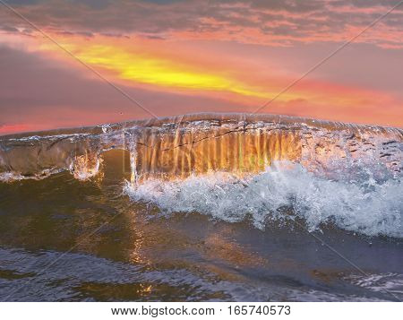 Big curling wave crashing in front of a beautiful sunset. Very clear clean water that looks very heavenly.