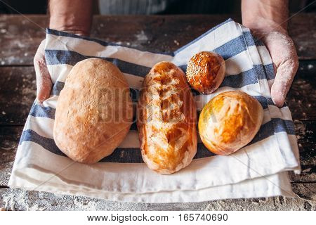 Baker holding fresh hot bread close-up. Warm fresh buns on kitchen towel in man hands. Homemade bakery, soft tack preparing, kitchen concept