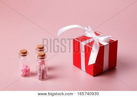 Valentine day composition: red gift box with bow and glass bottles with clamps buttons on light pink background.
