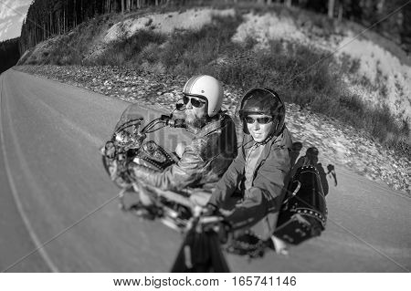 Biker riding his motorcycle on the road with the passenger looking to the camera. Man is wearing jacket helmet and sunglasses. Selfie style. Motion picture. Tilt lens blur effect. Black and white