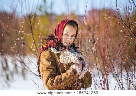 Fashion outdoor portrait of beautiful blonde woman clothed in scarf and sheepskin coat in the middle of willow willows. Russian national winter clothes.