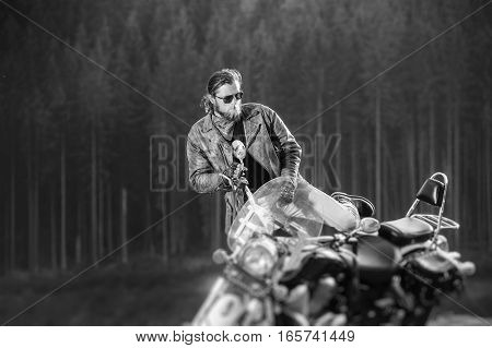 Handsome Biker Standing By His Custom Made Cruiser Motorcycle