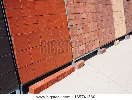 Stacks of various and for sale. Building and construction materials colored concrete pavers (paving stone) bricks and patio blocks organized on pallets for sale stored on metal shelves outdoors