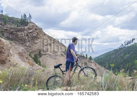 Young Man On Mountain Bike In The Mountains.