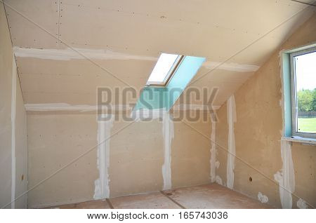Attic room under construction with gypsum plaster boards or Drywall. Attic room construction interior. Skylight window. Repair and attic renovation.