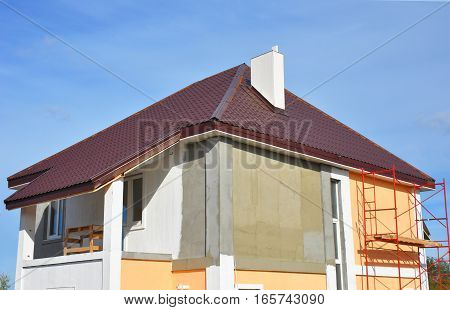 Construction or repair of the rural house with Balcony Eaves Windows Chimney Roofing Fixing fFcade Insulation Plastering and Painting Walls. Painting House Facade
