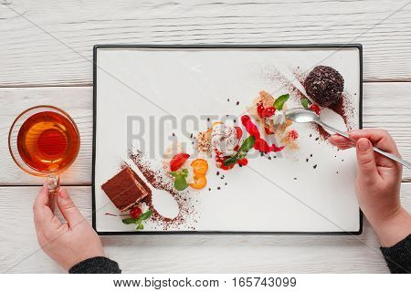 Sweet cakes mix eating, eater pov. Top view on man tasting desserts with cup of hot tea. Degustation, choosing dessert for party or wedding, gastronomy, event organization concept