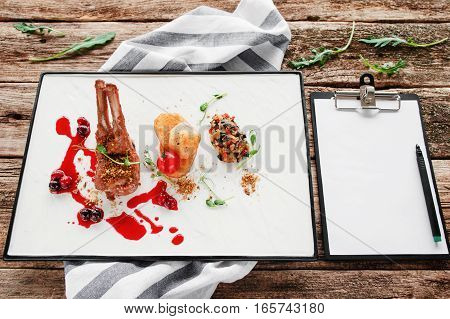 Expensive restaurant meal with blank notepad. Grilled ribs with vegetables and cherry sauce. Degustation, luxury lifestyle, choosing menu for party concept