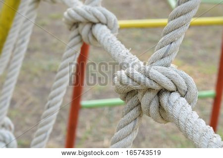 Close-up of rope knot line tied together with playground  background,as a symbol for trust, teamwork or collaboration.