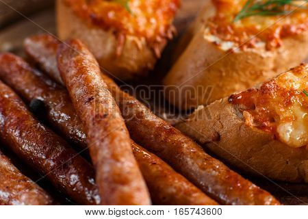 Bavarian sausages with canapes closeup. Appetizing fat snack for beer background. German cuisine, junk food, dieting concept
