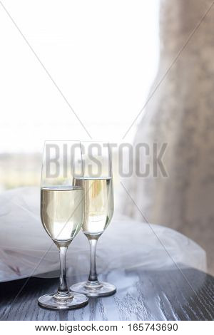 Two glasses of champagne near the wedding veil