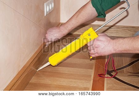 Repairman's hands Installing Skirting Board Oak Wooden Floor with Caulking Gun Silicone from Cartridge. Flooring with Wooden Batten Repair.