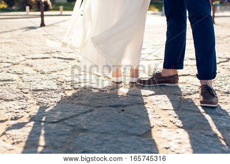 Newlyweds stand on a stone pavement together