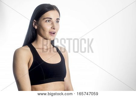 Beautiful girl. Fitness girl with an open mouth. Girl on a white background. Sport girl with space for text. Girl sports instructor