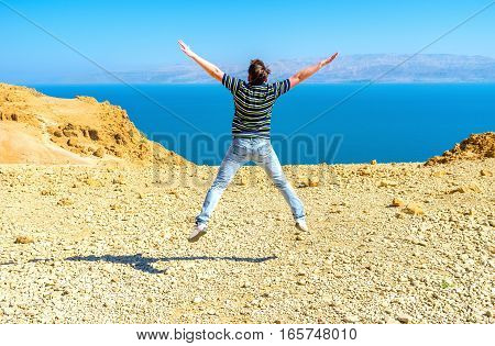 The star jump on the top of the mount in Judean Desert with the Dead Sea on the background Ein Gedi Israel.