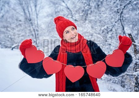 Love and valentines day concept. Smiling woman holding garland of five red paper hearts shape - blank copy space for letters or text, looking away over winter landscape