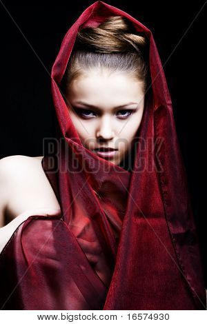 beautiful girl enveloped  in red headscarf. Fashion photo