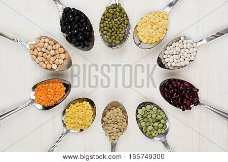 Decorative frame of assortment different beans in spoons with copy space on white wood background. Top view closeup.