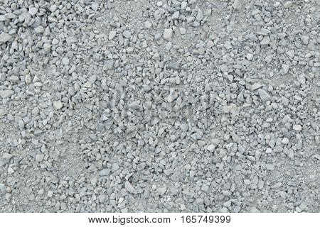 A pile of light gray gravel / aggregate of glauconite stone out of the crusher of a stonepit. Pieces of stones, rocks and sand of varying sizes and shapes.