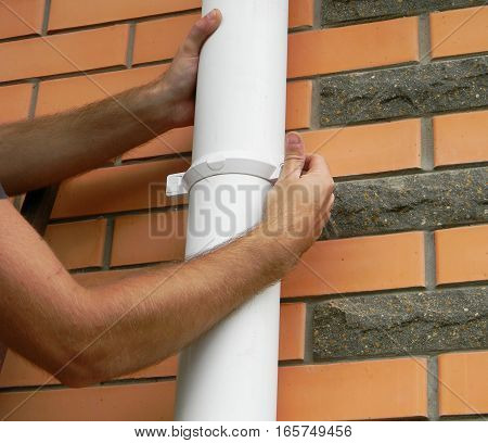 Man installing rain gutter system downspout pipe