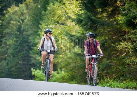 Happy Couple Ride On A Mountain Asphalt Road On Bikes