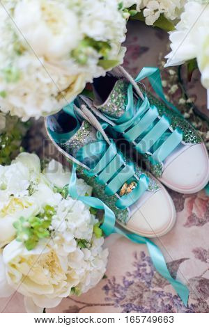Wedding rings, flowers and children's shoes composition