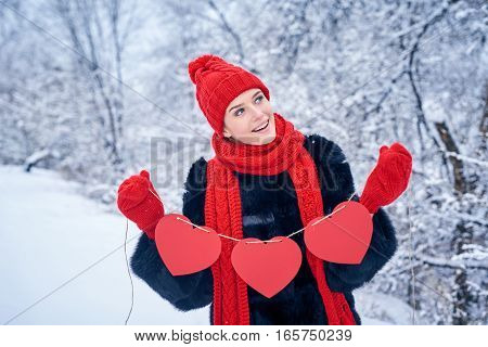 Love and valentines day concept. Smiling woman holding garland of three red paper hearts shape - blank copy space for letters or text, looking up over winter landscape