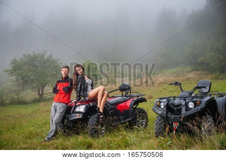 Happy Couple Near Four-wheeler Atv In Foggy Nature