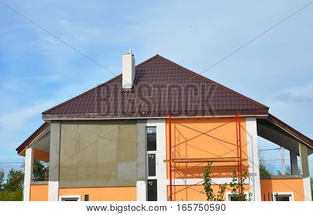 Construction or repair of the rural house with balcony eaves windows chimney metal tile roofing fixing facade insulation plastering, stucco and painting walls. Roofing Construction.