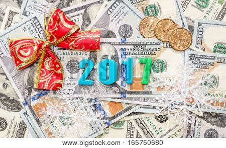 2017 text from plastic numbers with bow and coins on dollars background.