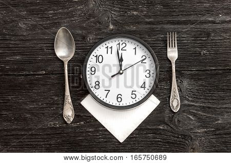 Clock on serviette with fork and spoon.Top view. Time to eat.