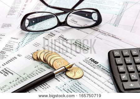 Pen glasses calculator and coins on tax forms. Business concept.